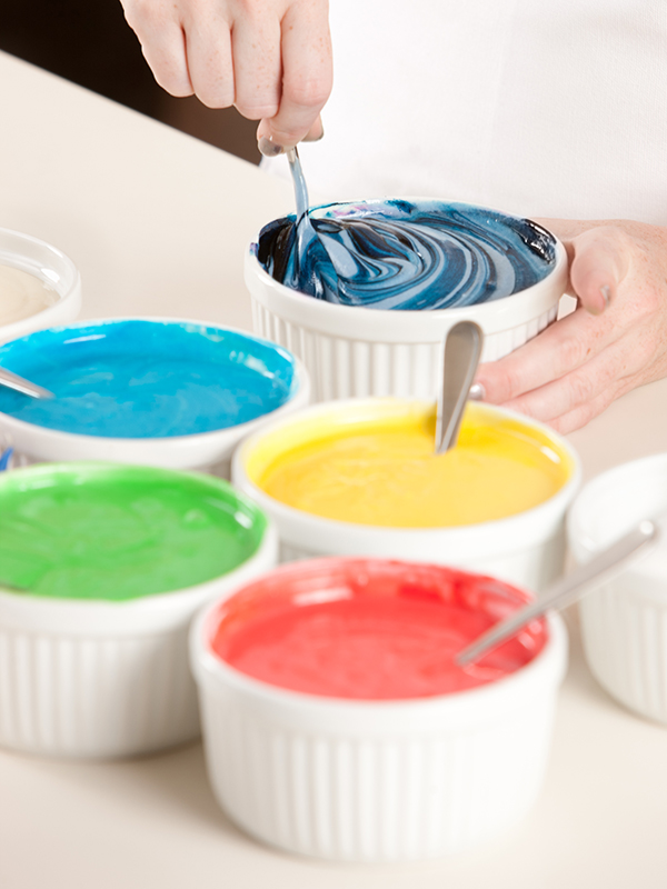A chef mixes the colorful batter to prepare the layers for a rainbow cake dessert. Extremely Shallow DOF.