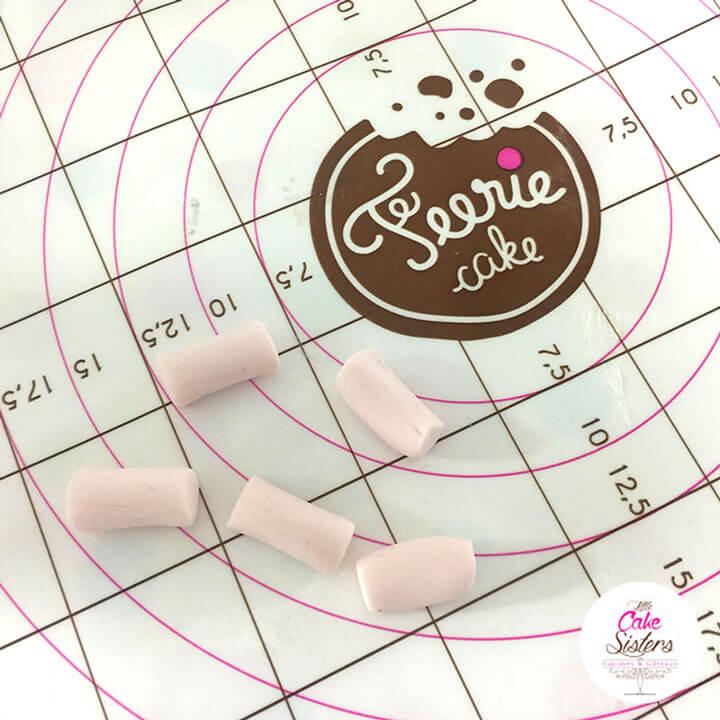 Découpez des petits rectangles irréguliers de pâte à sucre rose et blanche pour faire des mini marshmallows