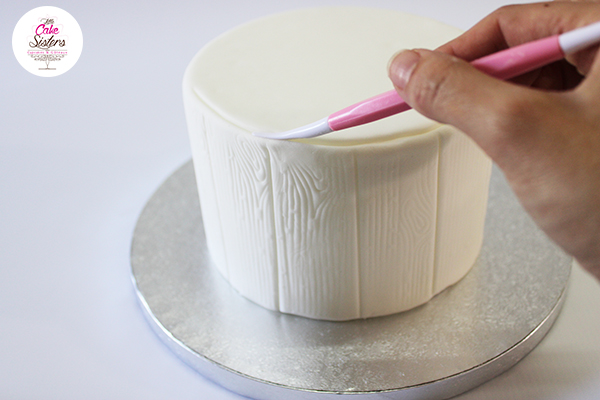Gâteau recouvert de pâte à sucre blanche effet tronc d'arbre