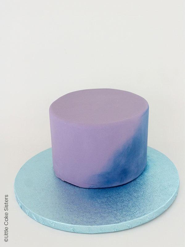 Couvrez votre gâteau avec votre pâte à sucre lilas, puis poudrez à l'aide d'un gros pinceau