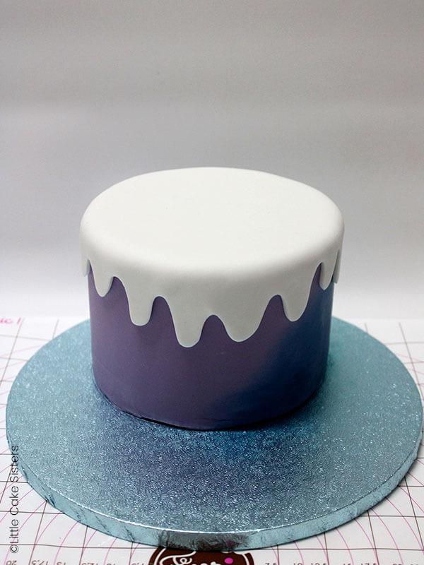 Mettez un peu de colle sur l'envers puis placez l'effet neige sur le haut de votre gâteau