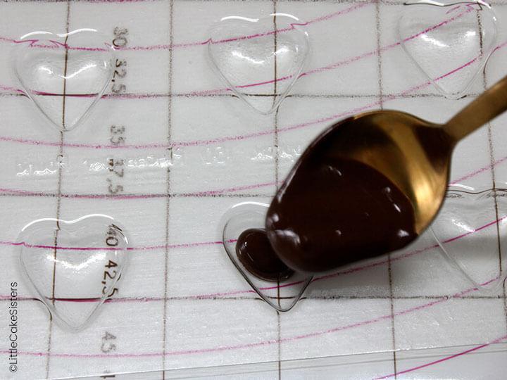 Coulez du chocolat fondu dans les moules en forme de cœur