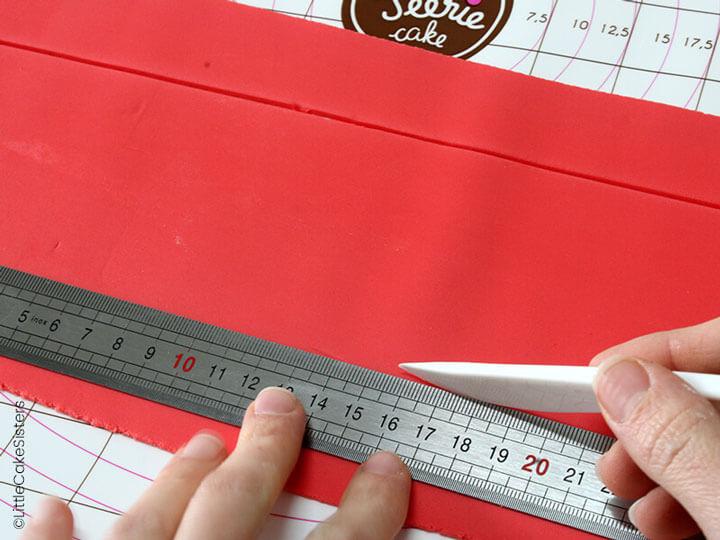 Pour le contour, découpez une bande de pâte à sucre rouge