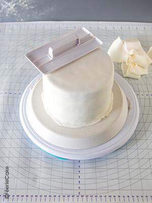 Lissage pâte à sucre sur un gâteau